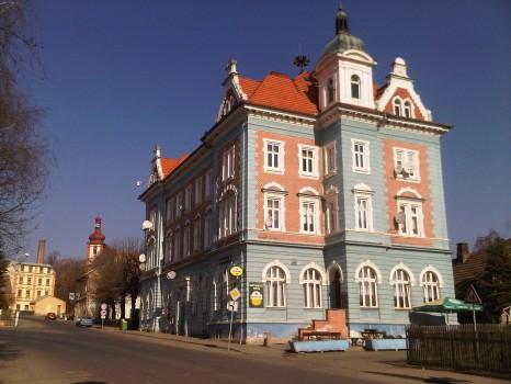 V pravo modrá budova pošty s restaurací a příjemným posezením.  Ulice Mostecká 75